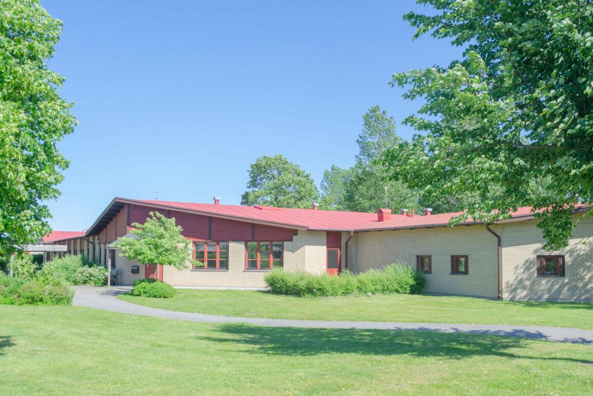 Gul tegelbyggnad med röda detaljer och tak.