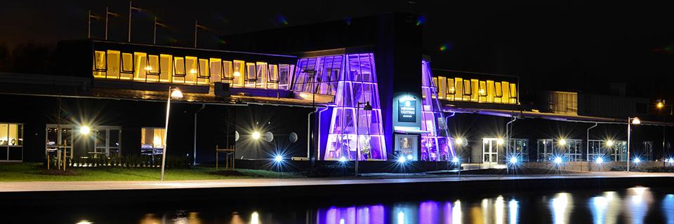 Kvällsbild på upplyst växthusbyggnad med återspegling i vatten