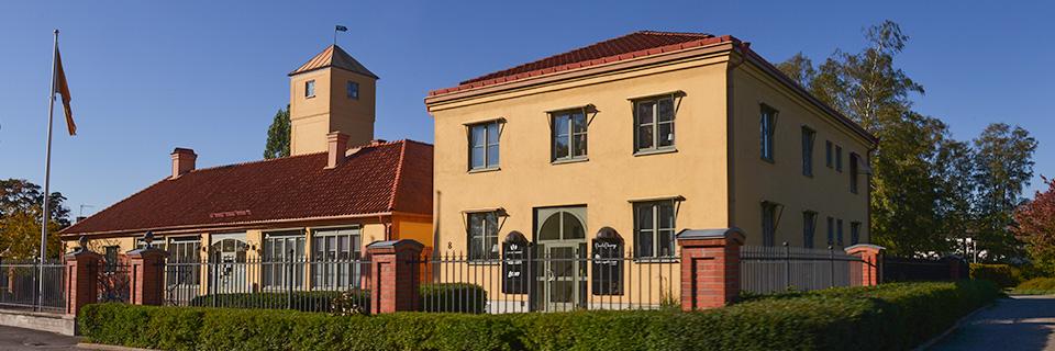 Gul byggnad med ett torn och rött tegeltak