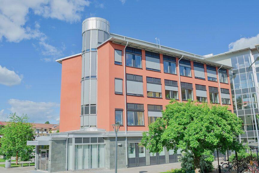 Röd 4-vånings kontorsbyggnad med grå stenfasad på bottenvåning.