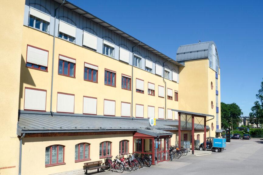 Gul fyra-våningsfastighet med blåa stendetaljer.