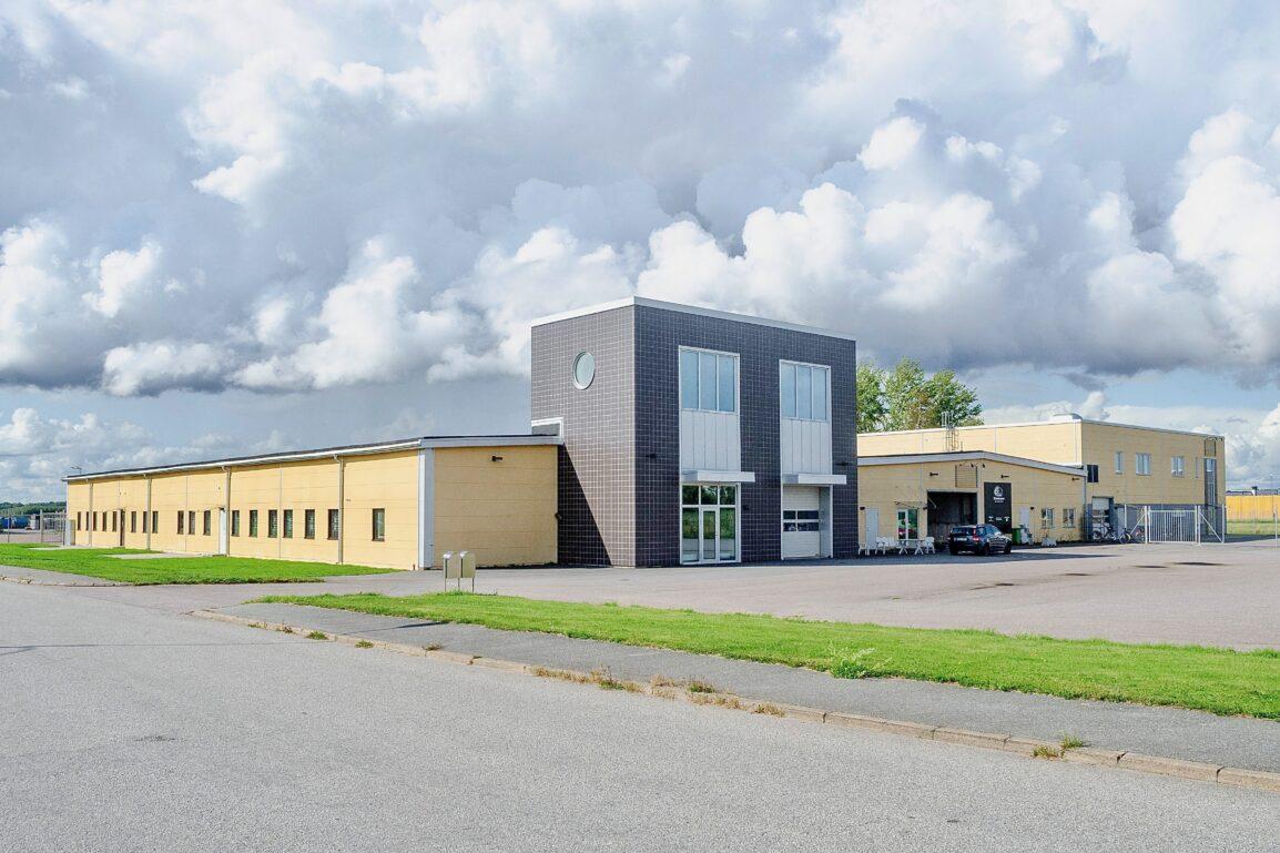 gul och grå verkstads- och lagerbyggnad.