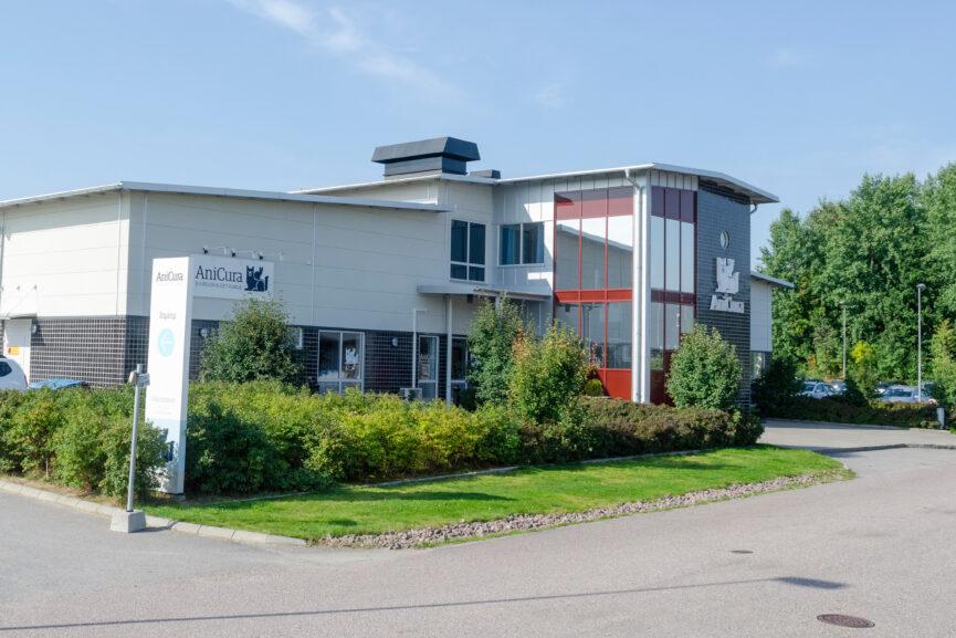 Vit och svart byggnad med röda detaljer vid entré fönsterpartierna djursjukhus