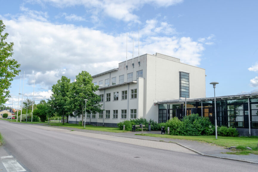 Vit tre-vånings kontorsbyggnad med svart enplans-entrédel.