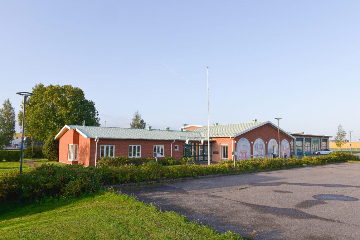 Röd tegelbyggnad med målningar i brandstationtema.