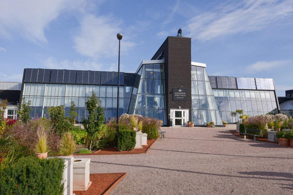 Svart växthusbyggnad med mycket glaspartier.