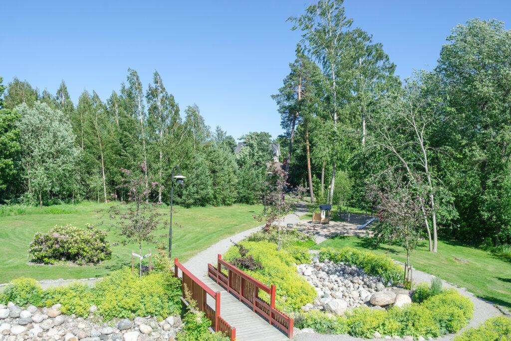 grönt parkområde med lekplats och röd trädbro över stenparti