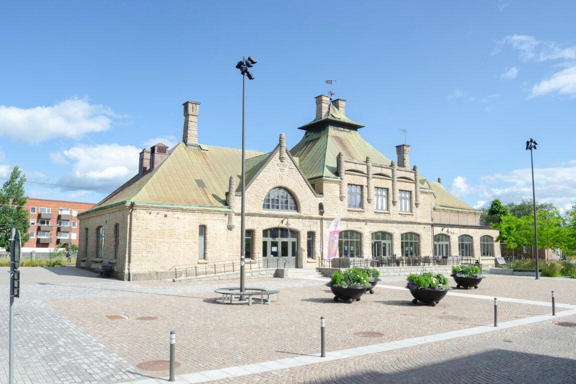Två-vånings stationsbyggnad med kalkstensfasad.