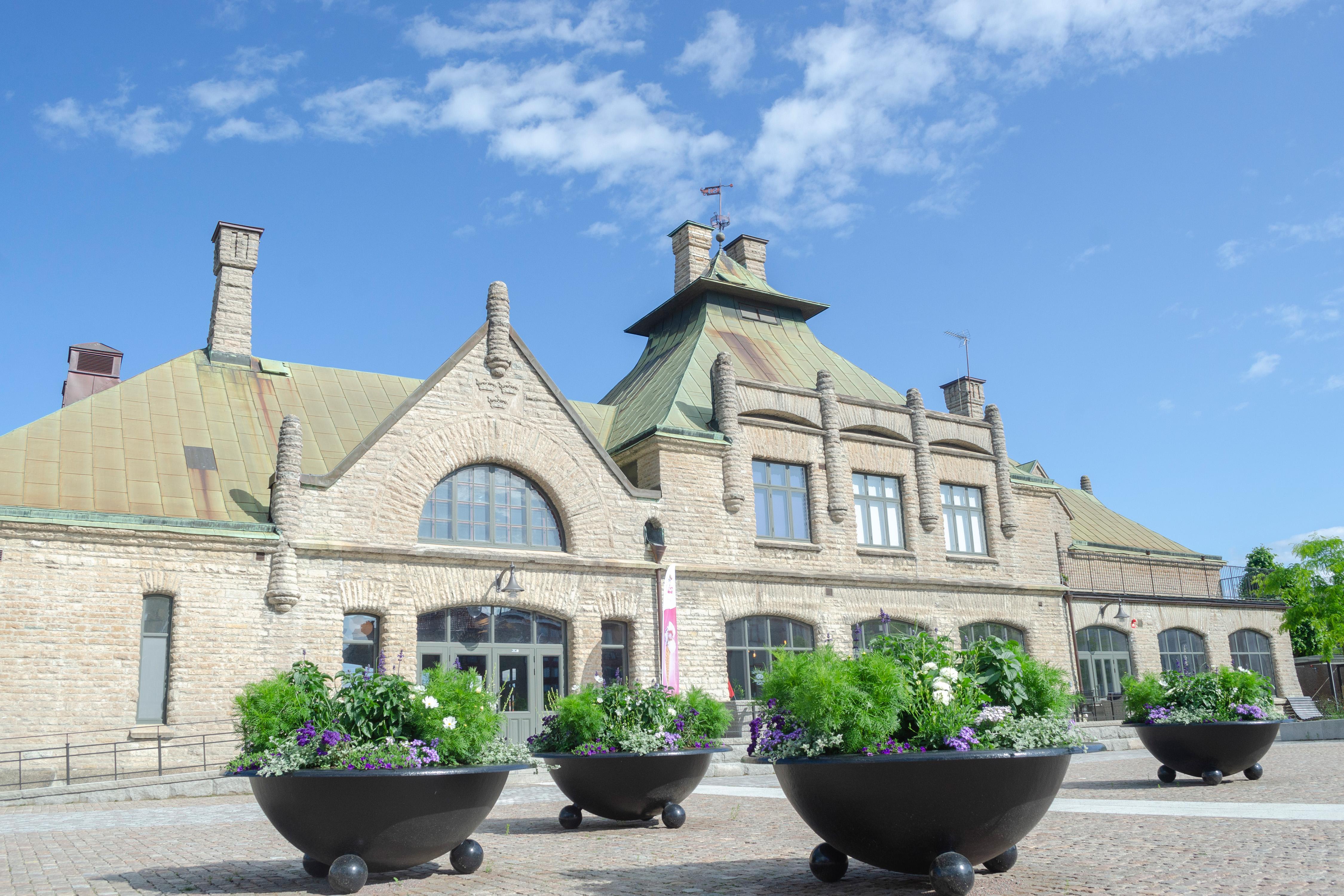 Stationsbyggnad med stenfasad och koppartak, tågstation.