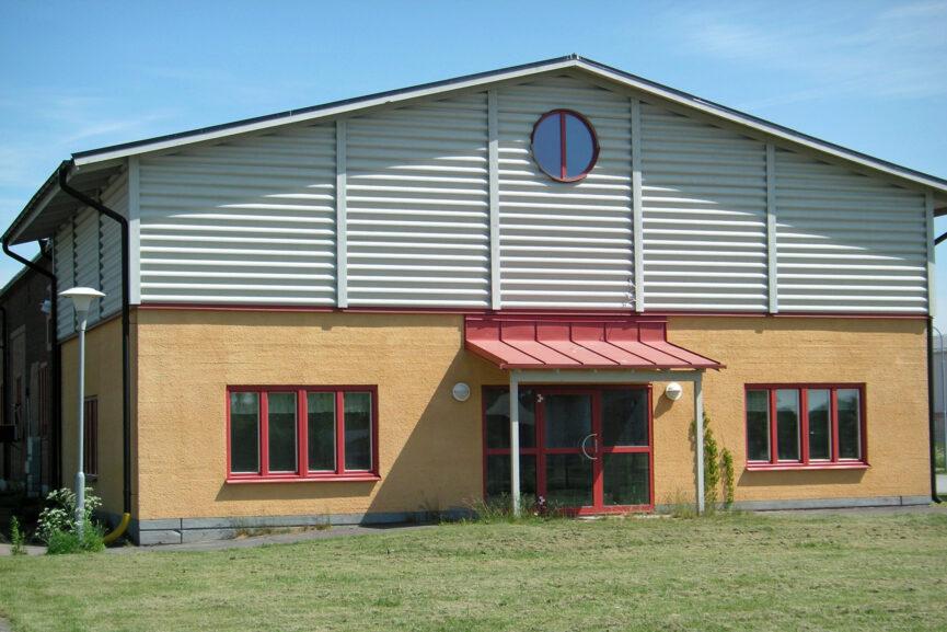 Gul kontorsbyggnad med plåtdetaljer.