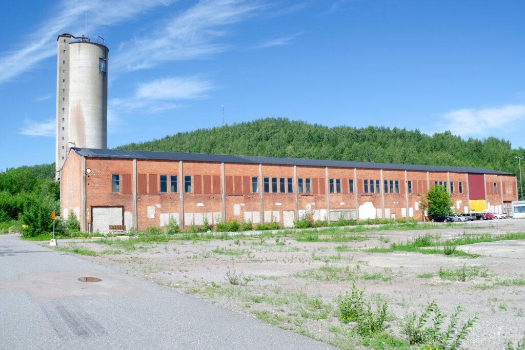 Äldre industribyggnad i rött tegel med hög cementskorsten.