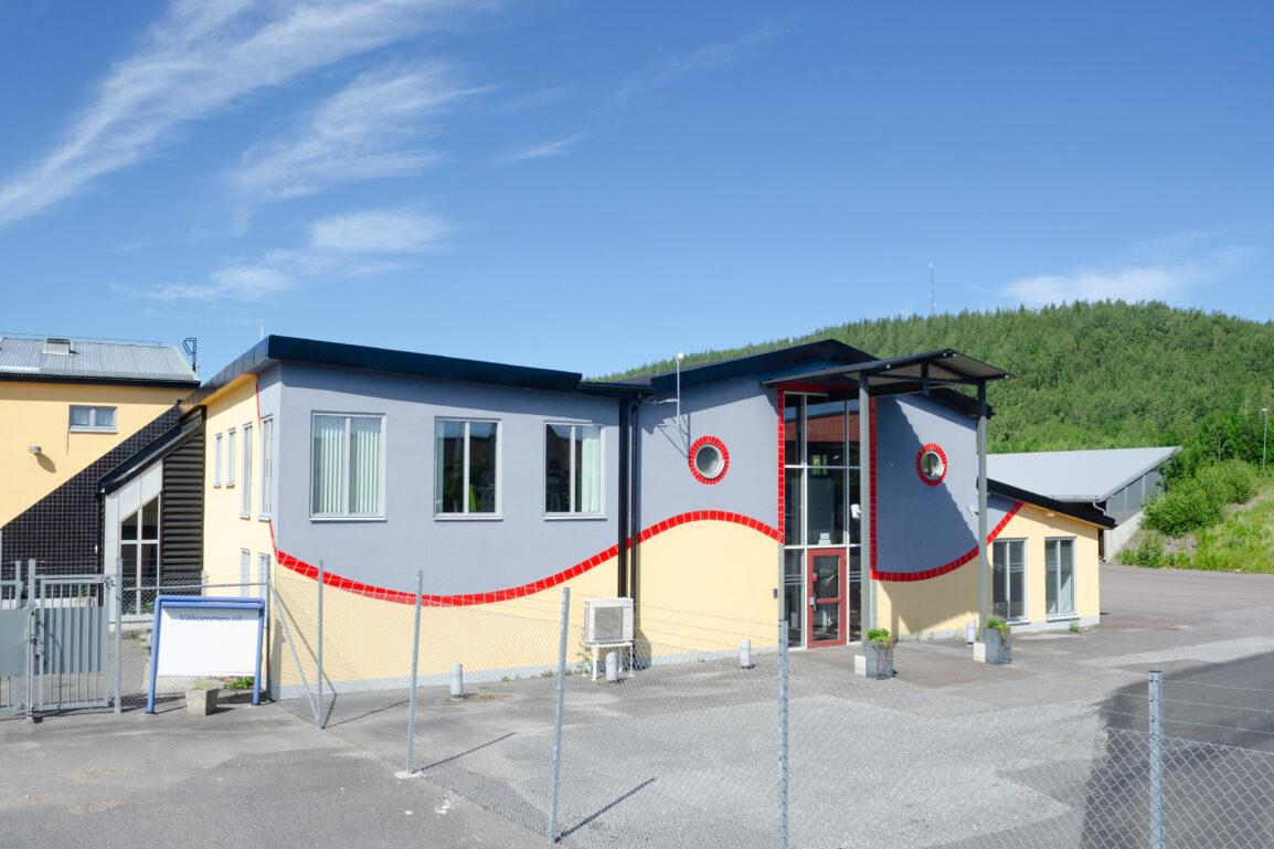 Gulgrå två-vånings kontorsbyggnad med röda detaljer