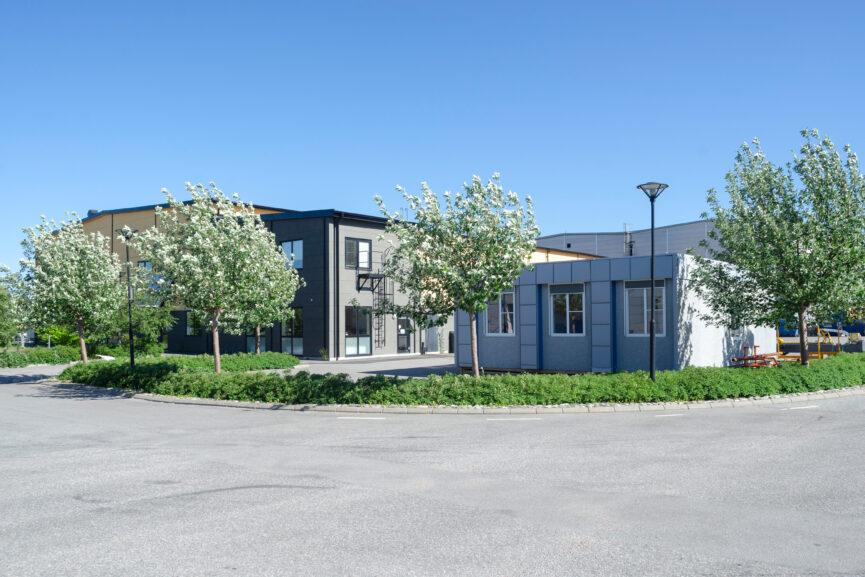 Gulgrå kontors- och industrifastighet med grå barack i förgrunden.