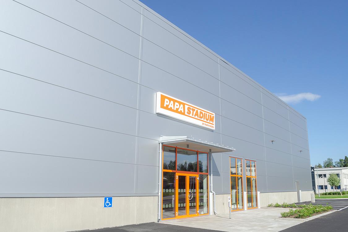 """Grå byggnad med en skylt i orange och vitt, """"Papa Stadium"""" ovanför den orangea entréen"""