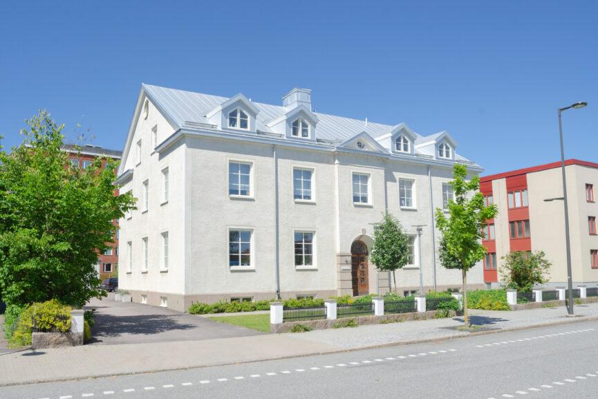 Vitputsad tre-vånings fastighet för bostäder och kontor.